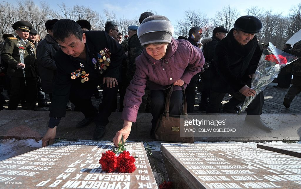 People lay flowers at a monument to the Kyrgyzstan born Soviet soldiers killed in Afghanistan while fighting against the Afghan rebels in the 1980s during a ceremony in the Kyrgyz capital Bishkek on February 15, 2013. The ex-Soviet nation of Kyrgyzstan marked today the 24th anniversary of the Soviet troops withdrawal from Afghanistan. AFP PHOTO/ VYACHESLAV OSELEDKO
