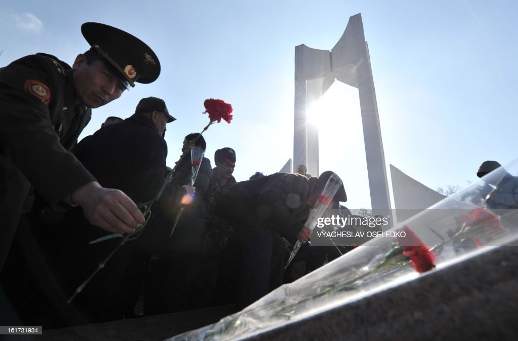People lay flowers at a monument to the Kyrgyzstan born Soviet soldiers killed in Afghanistan while fighting against the Afghan rebels in the 1980s during a ceremony in the Kyrgyz capital Bishkek on February 15, 2013. The ex-Soviet nation of Kyrgyzstan marked today the 24th anniversary of the Soviet troops withdrawal from Afghanistan.