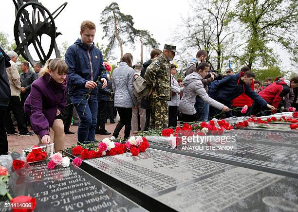 People lay flowers at the Chernobyl victims' memorial in the Ukrainian capital of Kiev on April 26 2016 Ukraine marks 30 years since the world's...