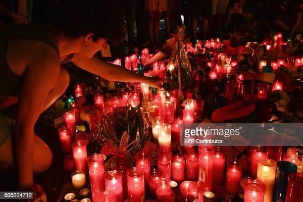 People lay flowers candles and other items at a makeshift memorial set up on the Las Ramblas boulevard in Barcelona as they pay tribute to the...