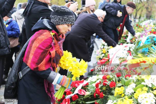People lay flowers especially yellow daffodils that signify remembrance of the Warsaw Ghetto Uprising during the 74th anniversary of the Warsaw...