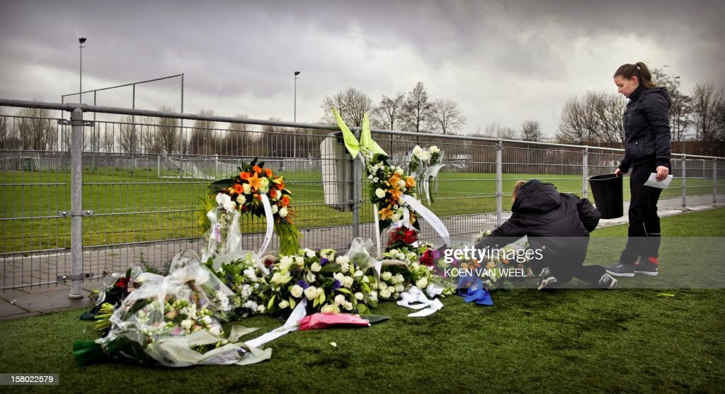 People lay flowers for linesman Richard Nieuwenhuizen at the clubhouse of Dutch football club SC Buitenboys in Almere, on December 9, 2012. Nieuwenhuizen collapsed and fell into a coma after he was attacked by three teenagers at the end of a junior club football match on December 2, 2012. People will gather this afternoon for a silent march in memory of Nieuwenhuizen. AFP PHOTO/ANP/ KOEN VAN WEEL netherlands out