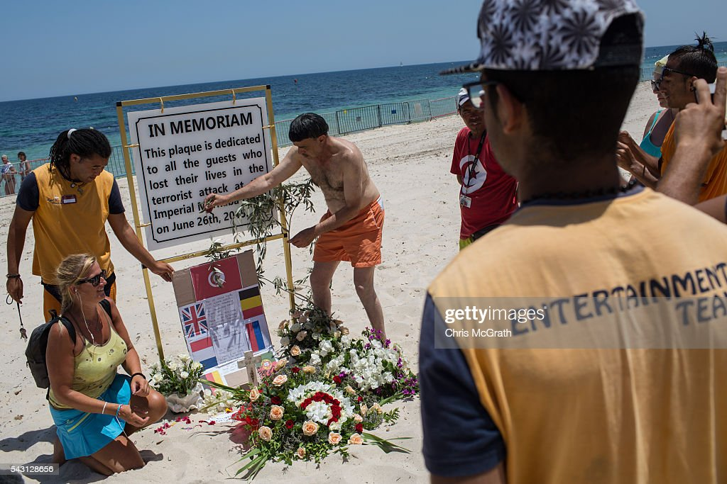 People lay flowers for the victims of the 2015 Sousse Beach terrorist attack at a memorial on the beach in front of the Imperial Marhaba hotel on June 26, 2016 in Sousse, Tunisia. Today marks the one year anniversary of the Sousse Beach terrorist attack, which killed 38 people including 30 Britons. Before the 2011 revolution, tourism in Tunisia accounted for approximately 7% of the country's GDP. The two 2015 terrorist attacks at the Bardo Museum and Sousse Beach saw tourism numbers plummet even further forcing hotels to close and many tourism and hospitality workers to lose their jobs.