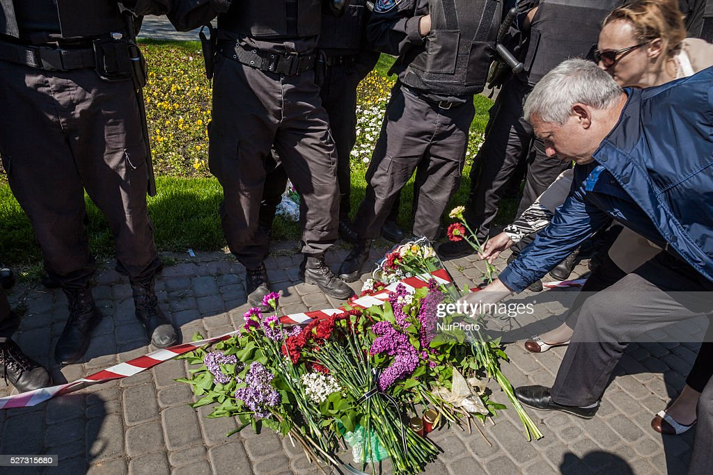 People lay flowers in front of the police riot in the entrance to Kulikovo Pole square in remembrance of the deaths of 2nd of May clashes in Odessa, southern Ukraine, on May 2, 2016, on 2014. The square was closed because a bomb threat.