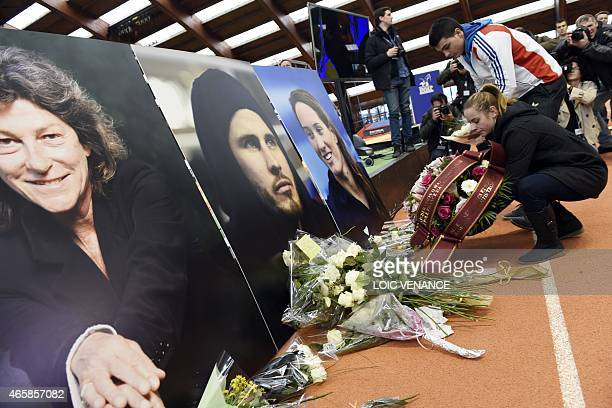 People lay flowers in front of the portraits of French late Olympic boxer Alexis Vastine Olympic champion swimmer Camille Muffat and yachtswoman...