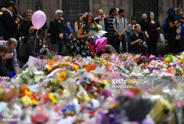 TOPSHOT People lay flowers in St Ann's Square after relocating them from Albert Square in Manchester northwest England on May 24 placed in tribute to...