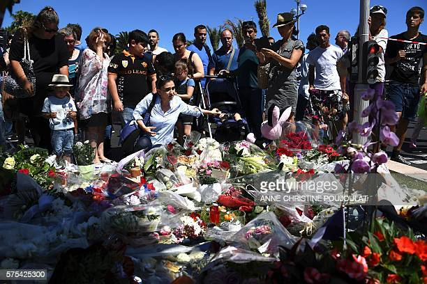 TOPSHOT People lay flowers in the street of Nice to pay tribute to the victims the day after a gunman smashed a truck into a crowd of revellers...