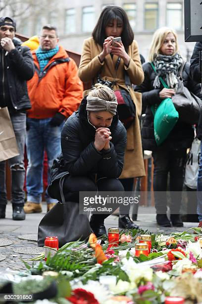 People lay flowers near where yesterday a lorry ploughed through a Christmas market on December 20 2016 in Berlin Germany So far 12 people are...