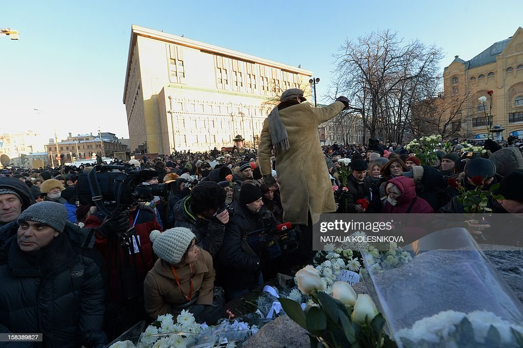 People lay flowers on a monument dedicated to victims of political repression during an opposition protest marking the first anniversary of the start of protests against Vladimir Putin, in Moscow, on December 15, 2012. Moscow police arrested 40 people today during this protest challenging Russian President Vladimir Putin, the force said in a statement on its website.