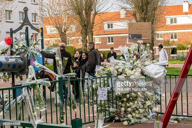 People lay flowers on a playground in homage to Chloe a nineyearold girl who was killed a day before on April 16 2015 in Calais northern France A...