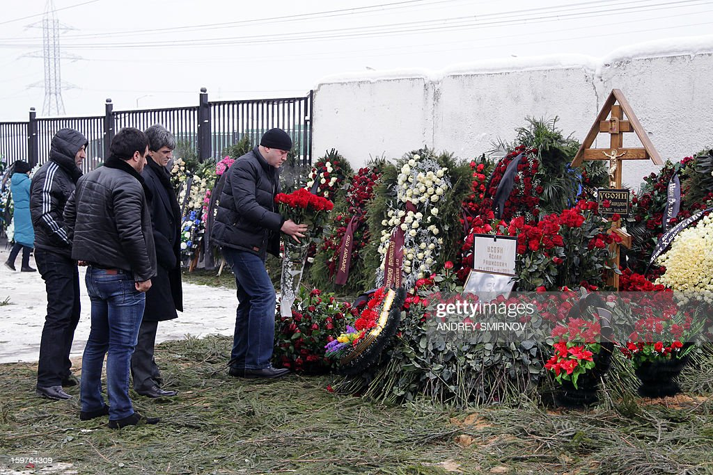 People lay flowers on the grave of Aslan Usoyan at Hovanskoye cemetery in Moscow on January 20, 2013.Russian crime boss Aslan Usoyan was buried in a tightly controlled ceremony in Moscow on Sunday, after efforts to fly his body to his hometown in Georgia fell through. Usoyan, 75, was the head of a gang that is reportedly the most powerful in the former Soviet Union.