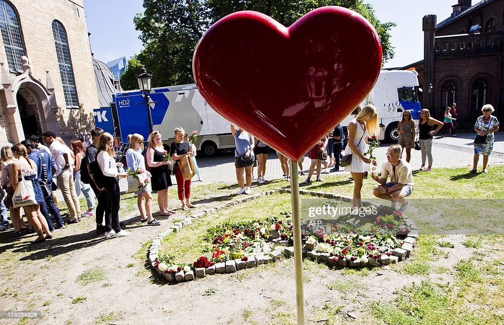 People lay flowers outside Oslo Cathedral, after the memorial service which took place to mark the second anniversary of the twin Oslo-Utoeya massacre by self confessed killer Anders Breivik on July 22, 2013 in Oslo.