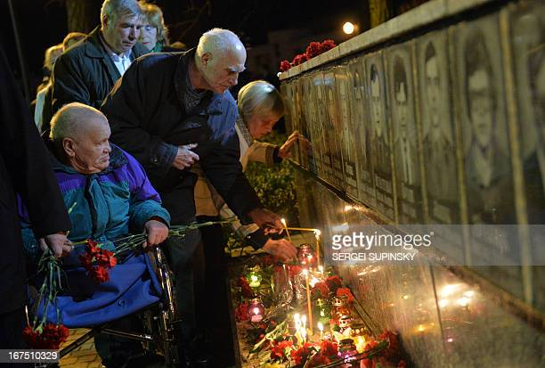 People lay flowers to portraits at the monument to Chernobyl victims in Slavutich some 50 kilometres from the accident site and where many of the...