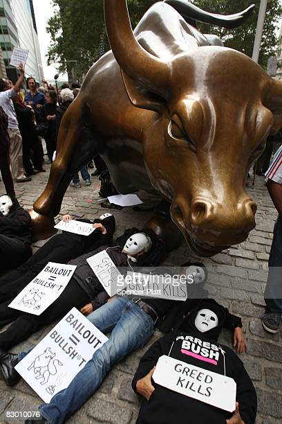 People lay underneath the iconic Wall Street bull during a rally in the financial district against the proposed government buyout of financial firms...