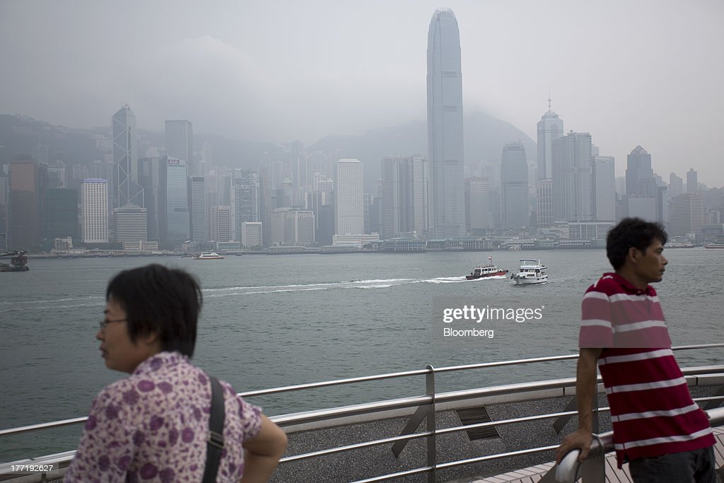 People lean on a railing on the waterfront in the Tsim Sha Tsui area of Hong Kong, China, on Thursday, Aug. 22, 2013. Hong Kongs air pollution index reached very high level today as a tropical storm that passed through Taiwan trapped pollutants and blanketed the city in haze, triggering a government health warning. Photographer: Jerome Favre/Bloomberg via Getty Images