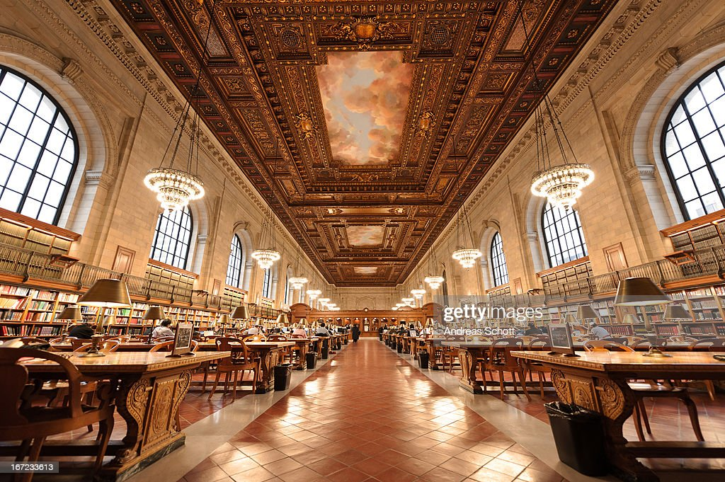 CONTENT] People learning on big tables in New York Public Library wide angle indoor shot lamps light up the room quiet room