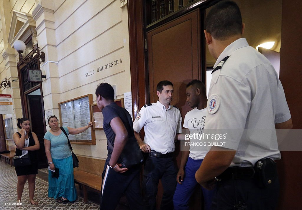 People leave a courtroom at Versailles' Courthouse, near Paris, on July 22, 2013 after the trial of three men for having thrown projectiles on Policemen during unrest in the suburban city of Trappes on July 19 evening. The unrest came after police officers carried out an identity check on a full-face veiled woman and her husband. The woman's husband tried to strangle one of the officers during the check according to Versailles' prosecutor. AFP PHOTO / FRANCOIS GUILLOT