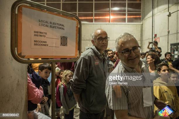 People leave a polling station after spending the night to oppose any attempt from police officers to close off this electoral centre as the Catalan...