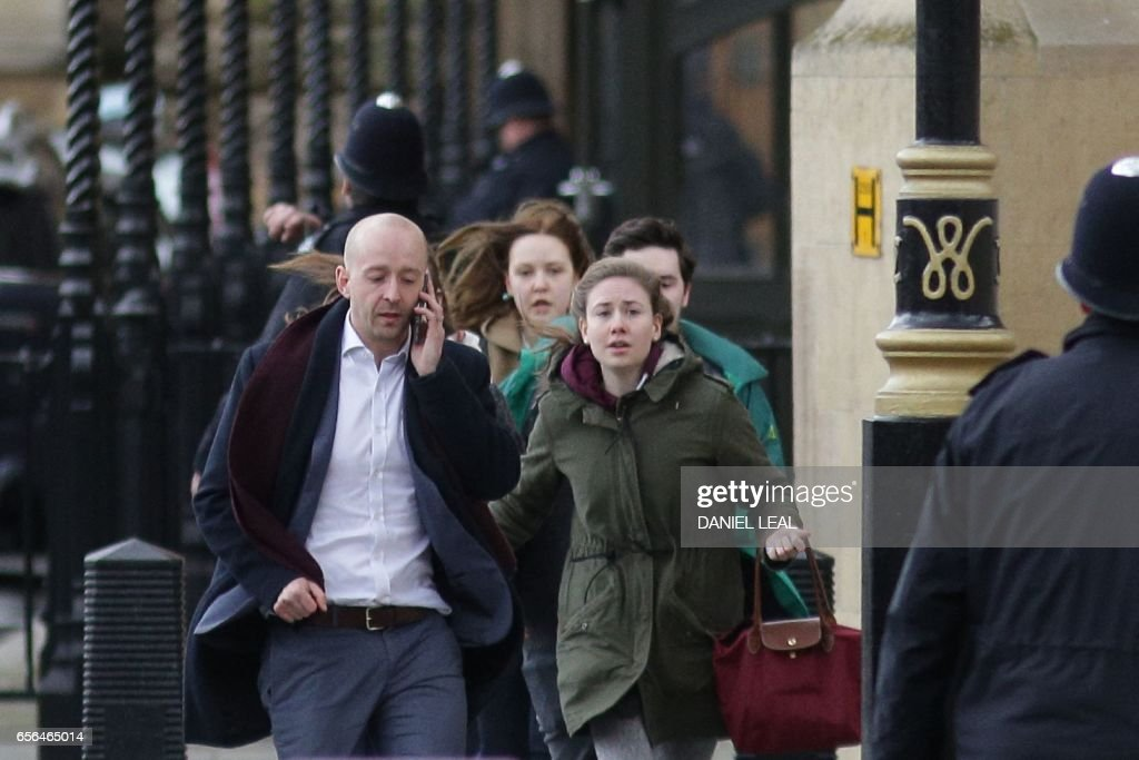 TOPSHOT - People leave after being evacuated from the Houses of Parliament in central London on March 22, 2017 during an emergency incident. Britain's Houses of Parliament were in lockdown on Wednesday after staff said they heard shots fired, triggering a security alert. / AFP PHOTO / Daniel LEAL
