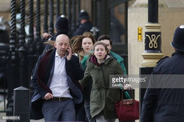TOPSHOT People leave after being evacuated from the Houses of Parliament in central London on March 22 2017 during an emergency incident Britain's...