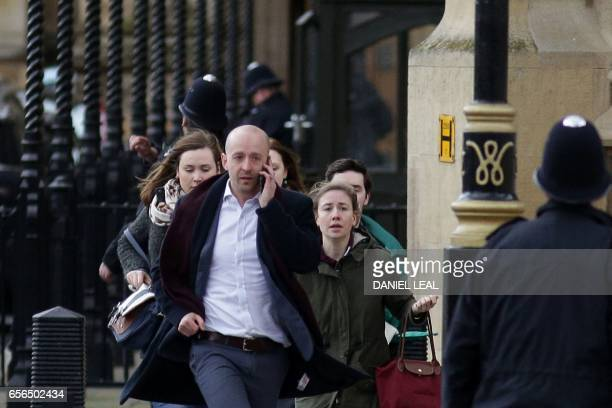 People leave after being evacuated from the Houses of Parliament in central London on March 22 2017 during an emergency incident British police shot...