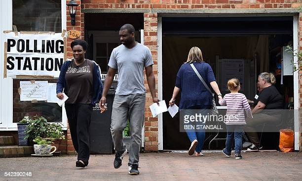 People leave after casting their votes in the EU referendum at a polling station set up in a residential garage in Croydon south of London on June 23...