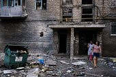 People leave an apartment building after shelling in the town of Yasynuvata near the rebel stronghold of Donetsk on August 12 2014 AFP PHOTO /...
