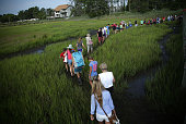 People leave as they walk in the marsh after they watched wild ponies swimming across the Assateague Channel during the annual pony swim event from...