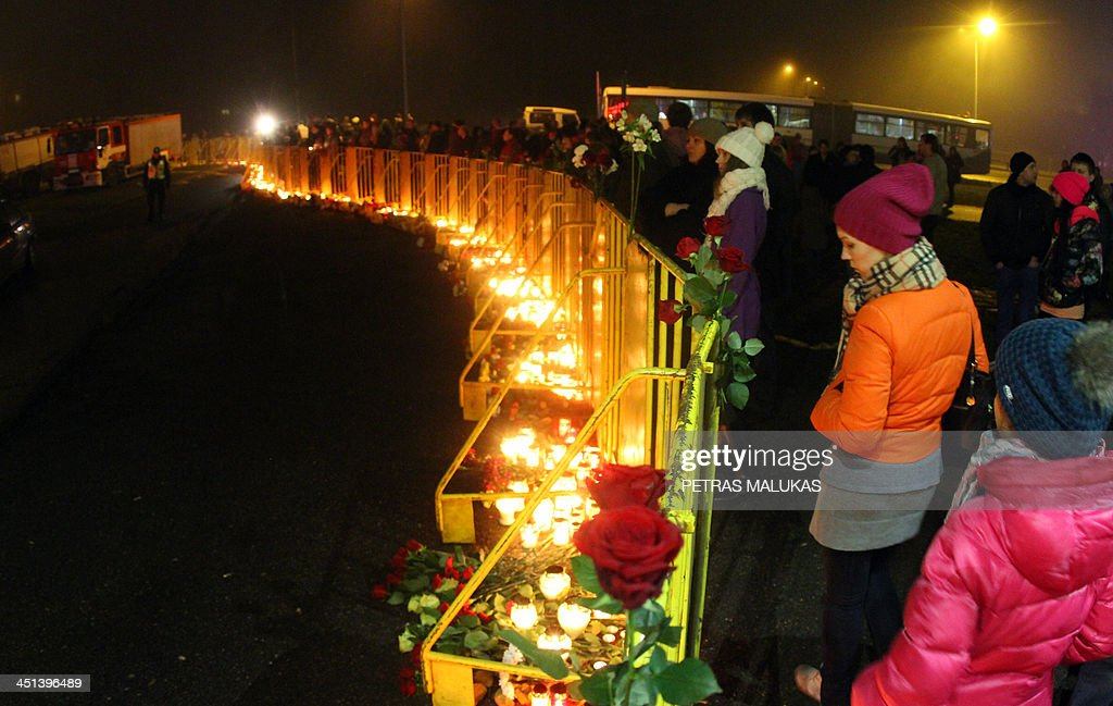 People leave flowers and candles at the scene where the Maxima supermarket roof collapsed in Riga on November 22, 2013. Fourty seven were killed and around 40 others injured when the roof of a supermarket collapsed a day earlier in a suburb of Latvia's capital Riga, emergency services said.