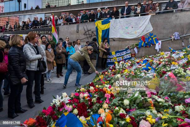 People leave flowers and pay their respects on Sergels square during a peace manifestation on April 9 2017 in Stockholm Sweden An Uzbek man has been...