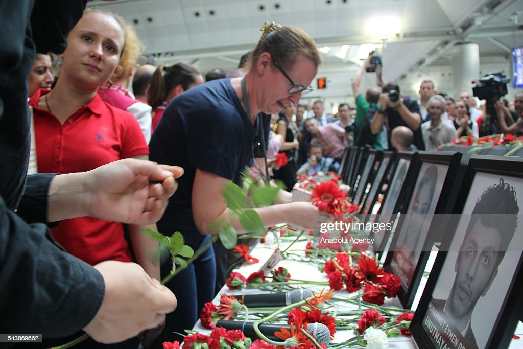 People leave flowers during a commemorative ceremony, held for the victims of the Istanbul Airport terrorist attack at International arrivals terminal in Istanbul, Turkey on June 30, 2016.