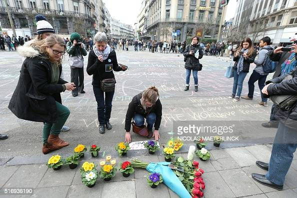 People leave messages and flowers in tribute to victims of triple bomb attacks in front of the stock exchange building in the city center of Brussels...