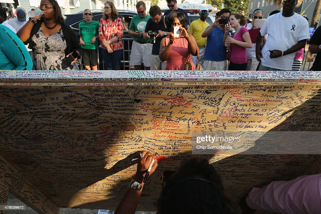 People leave messages of hope and encouragement in whatever space they can find on a large board in front of the historic Emanuel African American Methodist Church, four days after nine of its members were shot to death in the building, June 21, 2015 in Charleston, South Carolina. Church elders decided to hold the regularly scheduled Sunday school and worship service as they continue to grieve the shooting, which was allegedly carried out by a 21-year-old white supremacist who wanted to start a 'race war.'