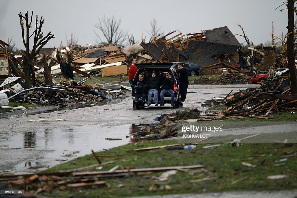 People leave on a truck after recovering belongings from a destroyed home on May 21, 2013 in Moore, Oklahoma. Families returned to a blasted moonscape that had been an American suburb Tuesday after a monstrous tornado tore through the outskirts of Oklahoma City, killing at least 24 people. Nine children were among the dead and entire neighborhoods vanished, with often the foundations being the only thing left of what used to be houses and cars tossed like toys and heaped in big piles. AFP PHOTO/Joshua LOTT