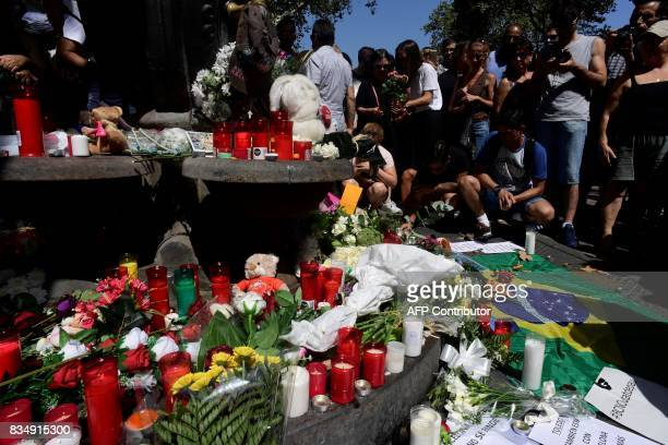 People leave stuffed toys candles messages flowers and other objects at the Canaletas fountain on the Rambla boulevard for the victims of the...