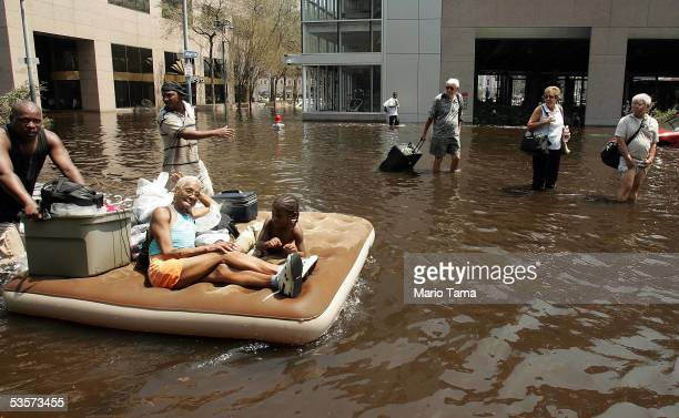 People leave the Superdome in the hopes of catching a ride out of town after Hurricane Katrina August 31 2005 in New Orleans Thousands of others were...