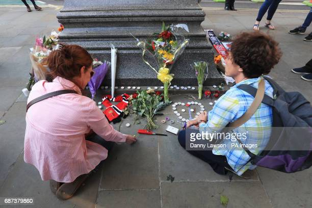 People leave tributes in Albert Square outside Manchester Town Hall after a 23yearold man was arrested in connection with the Manchester concert bomb...