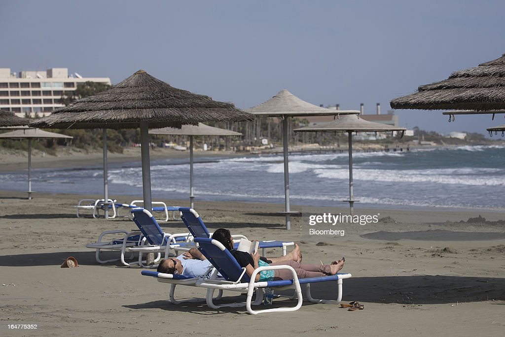 People lie on sunloungers on the private beach at St Raphael resort hotel in Limassol, Cyprus, on Wednesday, March 27, 2013. Directly or indirectly, tourism makes up a quarter of Cyprus's economy with visitors from the two main tourism markets, Germany and U.K. Photographer: Simon Dawson/Bloomberg