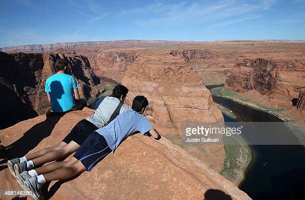 People lie on the edge of a cliff to view the Colorado River at Horseshoe Bend on March 30 2015 in Page Arizona As severe drought grips parts of the...