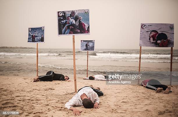 People lie on the Gaza beach to commemorate Aylan Kurdi the threeyearold boy dressed in shorts and a red Tshirt and 12 Syrians who drowned in the...