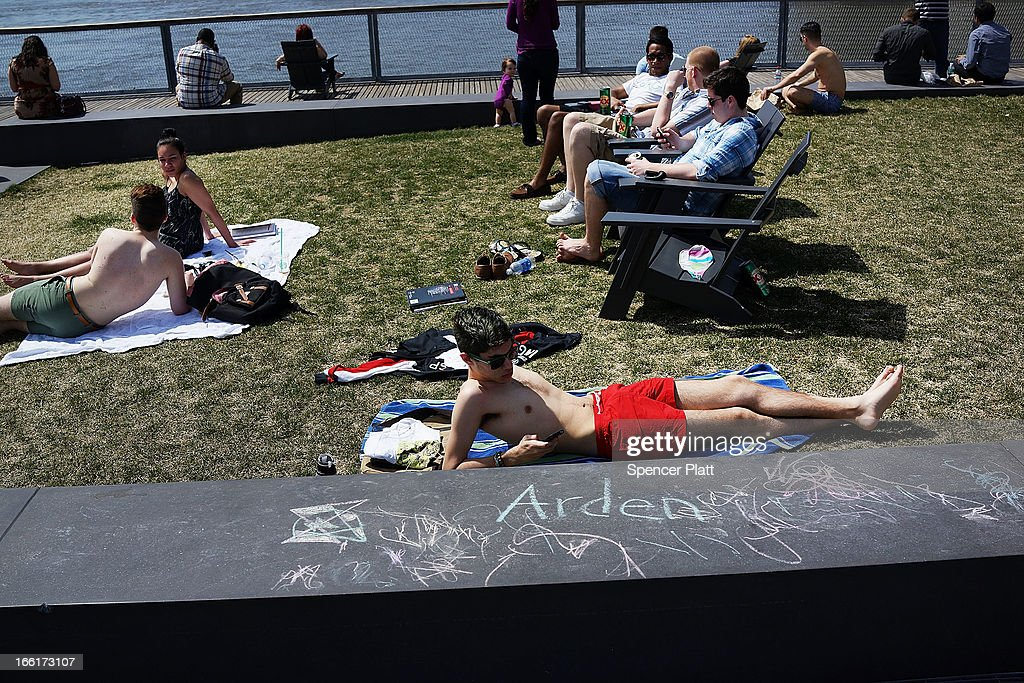 People lie on the grass along the East River in lower Manhattan during warm weather on April 9, 2013 in New York City. For the first time since October, temperatures are expected to rise above 70 degrees this week in New York and surrounding areas.
