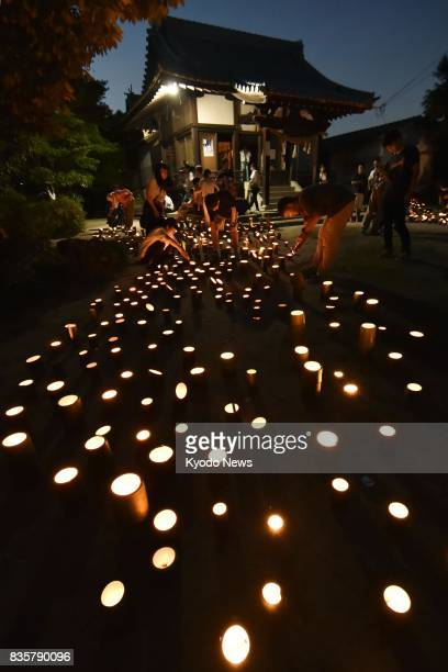 People light bamboo lanterns and fall silent in honor of victims of landslides in the western Japan city of Hiroshima on Aug 20 the third anniversary...