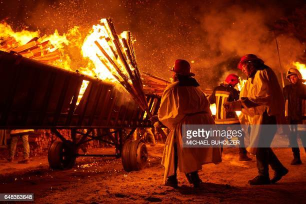 People light bundles of pinewood chips during the 'Chienbase' procession on March 5 2017 in Liestal northern Switzerland The procession takes place...