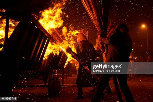 TOPSHOT People light bundles of pinewood chips during the 'Chienbase' procession on March 5 2017 in Liestal northern Switzerland The procession takes...