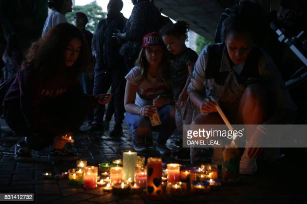 People light candles after a silent march in memory of the victims of the Grenfell Tower fire in west London on August 14 2017 The march marks two...