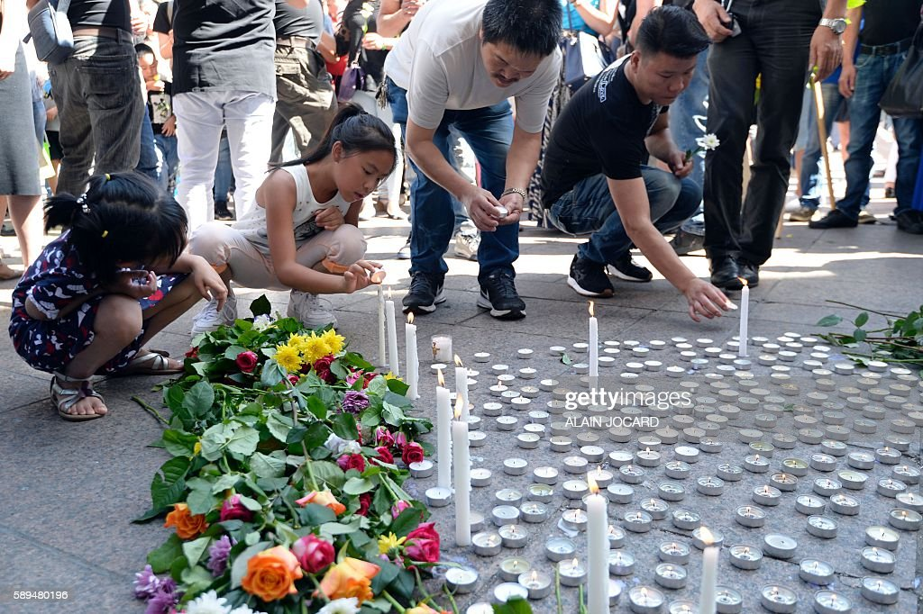 People light candles and lay flowers during a tribute ceremony to Chinese Zhang Chaolin outside the city hall in Aubervilliers northeastern suburbs...