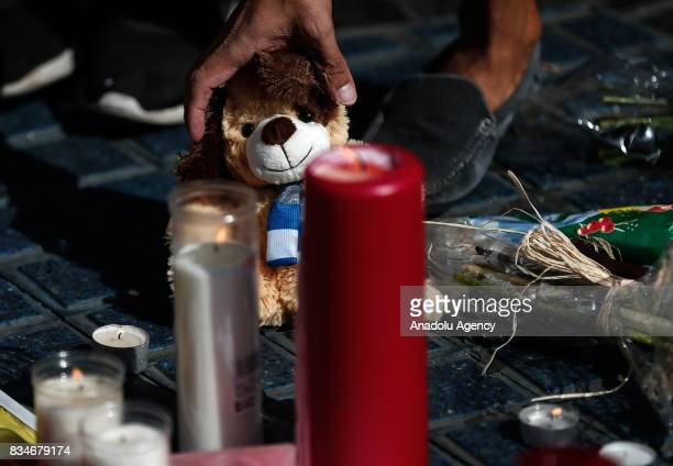 People light candles and leave flowers at La Rambla boulevard for the victims those who lost their lives in terror attack killing at least 13 people...