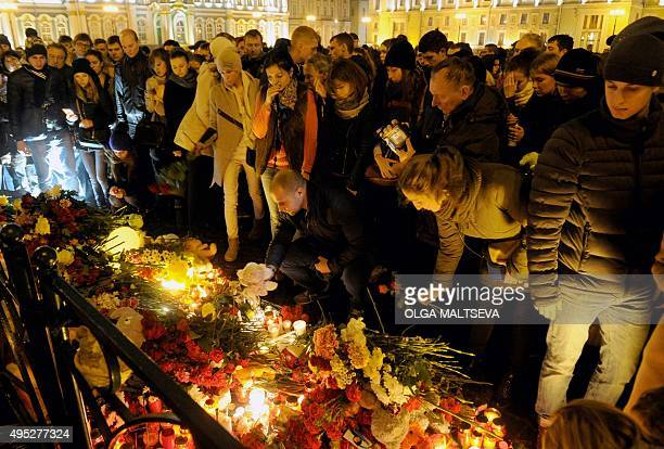 People light candles and place flowers in central Saint Petersburg on November 1 in memory of the victims of a jetliner crash Flags flew at halfmast...
