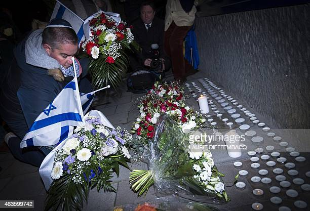 People light candles and place Israeli flags on February 16 2015 in front the Danish Embassy in Brussels for the the victims of weekend attacks on a...