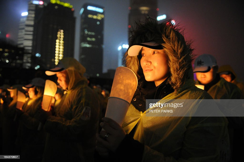 People light candles as they take part in an event to promote 'Earth Hour' in the financial district of Shanghai on March 23, 2013. Iconic landmarks and skylines were plunged into darkness as the 'Earth Hour' switch-off of lights around the world got under way including China's commercial hub of Shanghai to raise awareness of climate change. AFP PHOTO/ Peter PARKS